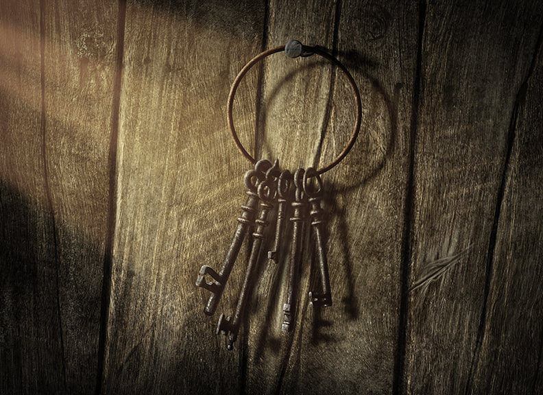 Several keys hang from a large, old brass keyring. The keyring hangs from a rusty hook on a wooden wall.